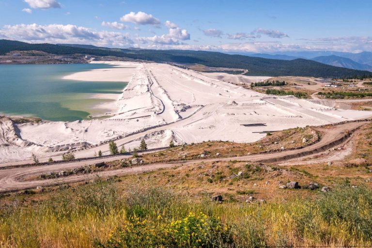 Barragem de rejeitos com lago à esquerda e montanhas ao fundo