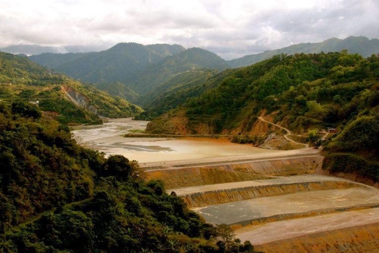 Barragem de rejeitos de mineração com mata verde e montanhas ao fundo