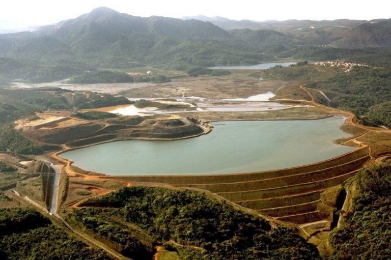 Vista panorâmica de uma barragem de rejeitos de mineração com um lago de água no centro e montanhas verdes ao fundo