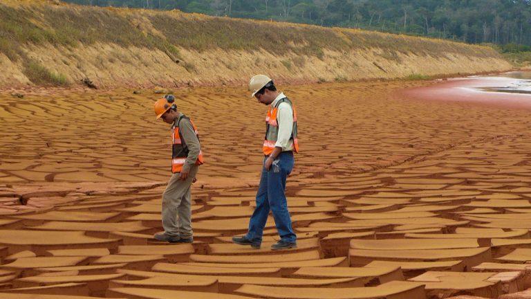 Dois homens caminhando sobre solo rachado em reservatório de barragem