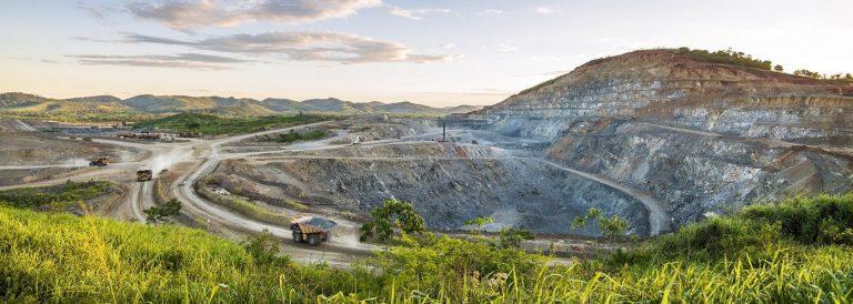 Cava de mina a céu aberto com equipamentos pesados circulando no local