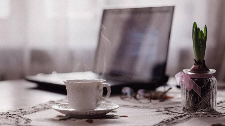 Imagem de um computador e uma xícara de café em um ambiente caseiro exemplificando o Home Office