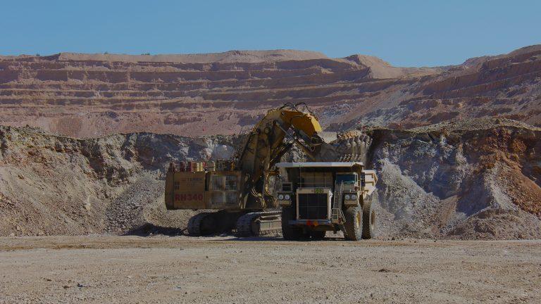Carregadeira carrega caminhão em mina