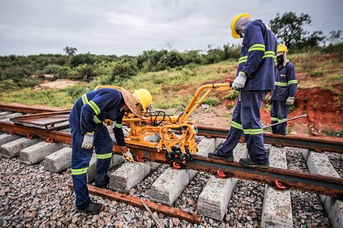 Fotografia de homens trabalhando em uma ferrovia